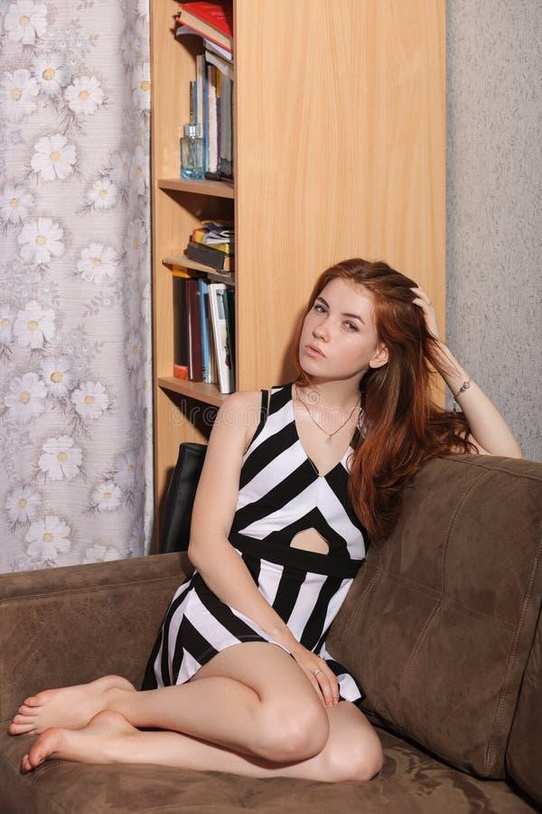 Spontaan portret van de nadenkende jonge mooie zitting van de roodharigevrouw op bank wat betreft haar schitterende achtergrond v royalty-vrije stock foto