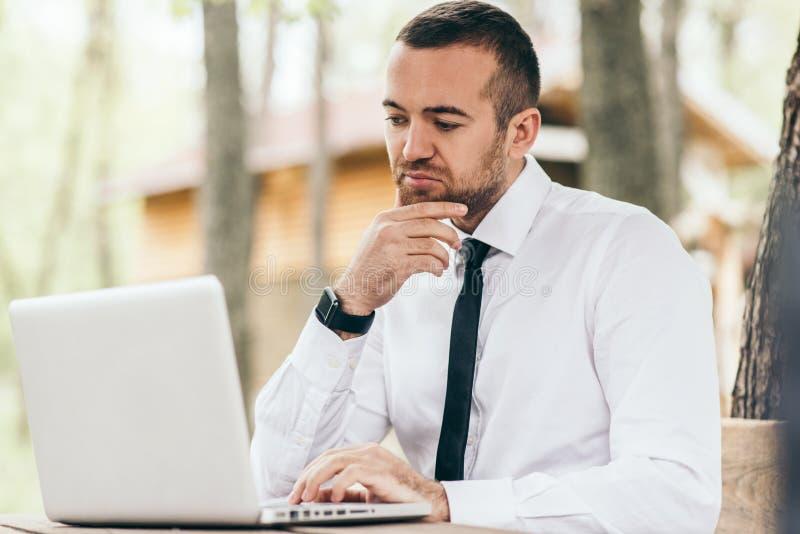 Spontaan schot van ernstig en geconcentreerd jong Kaukasisch die managergevoel, zitting bij openlucht met generische laptop PC wo stock foto's