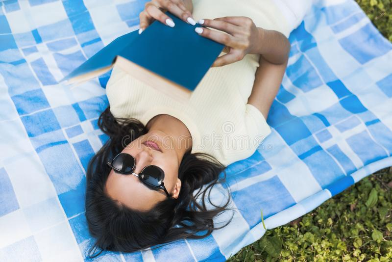 Spontaan schot van het jonge Kaukasische donkerbruine vrouw liggen op groen gras met een boek tijdens picknick in het park Mooie  stock foto