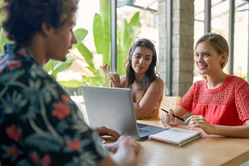 Spontane die levensstijl van drie diverse millennial vrienden wordt geschoten die aan laptop computer in heldere moderne koffie s stock foto