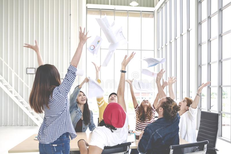 Spontane groep jonge creatieve documentendocument werpen en teamwerknemer die prople gelukkig na het werksucces op werkende plaat royalty-vrije stock foto's