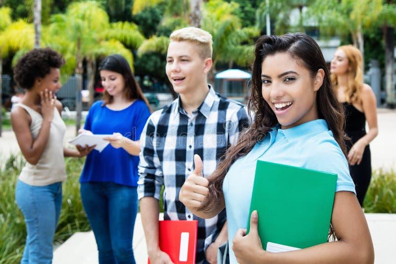 Spontane Latijns-Amerikaanse vrouwelijke student met groep studenten stock foto