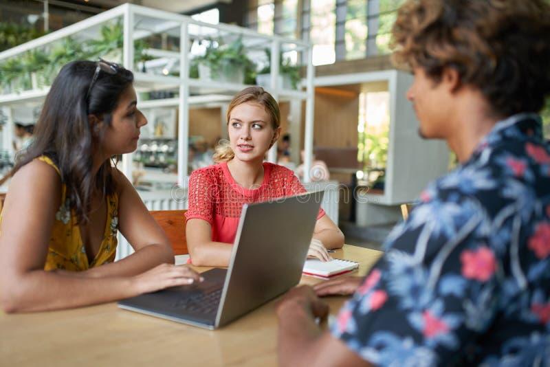 Spontane levensstijl die van het multi-etnische millennial collegagroep bespreken samen op laptop computer bij een lijst binnen w royalty-vrije stock fotografie