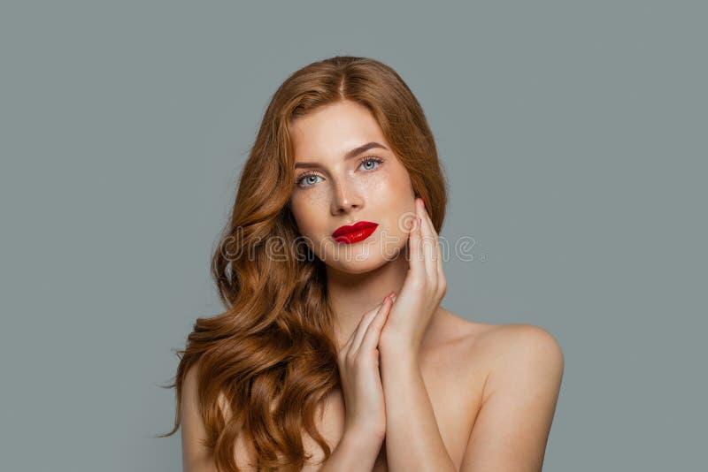 Spontane roodharigevrouw Rood haired meisje met gezond krullend haar op blauwe achtergrond stock afbeeldingen