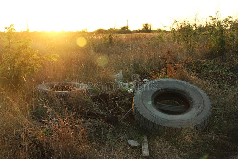Spontaneous dump discarded tires and household rubbish . garbage dump on the side of a dirt road. The problem of recycling garbage. Tires and environmental stock photography