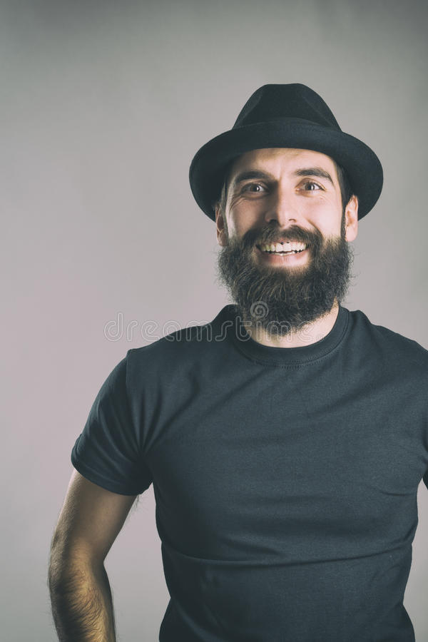 Spontaneously laughing bearded hipster wearing black t-shirt and hat looking at camera. Retro toned filtered portrait over gray background with vignette effect royalty free stock photography