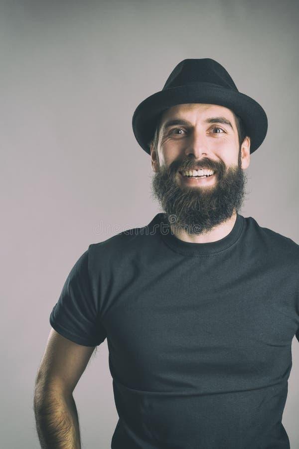 Spontaneously skratta den skäggiga hipsteren som bär den svarta t-skjortan och hatten som ser kameran royaltyfri fotografi