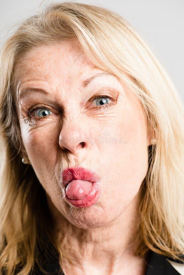 Bakgrund för grå färg för definition för kick för rolig kvinnastående verkligt folk arkivbilder