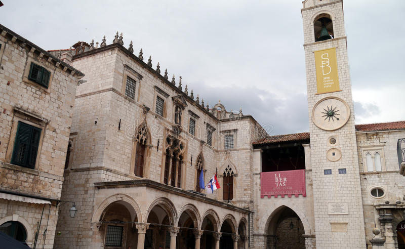 Sponza, Palace in Dubrovnik. Sponza, Palace, in Dubrovnik, Old Town, with Croatian, and Euro flags. Arches, Croatian flag, Euro flag and tower stock photo