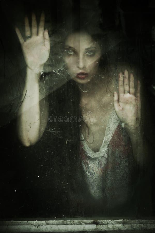 Spookachtig vrouwenportret achter oud houten venster stock foto
