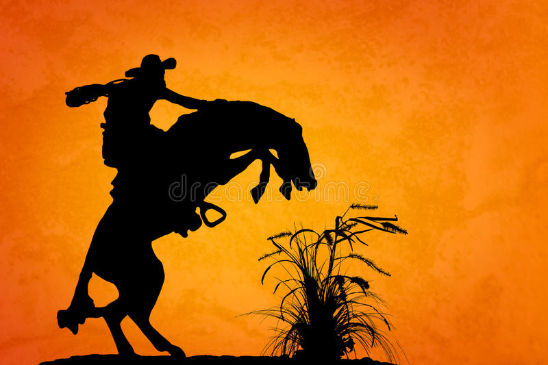 Spooked Stallion. Silhouette of cowboy reigning bucking bronco spooked by something in the nearby sagebrush. Sunset orange/yellow textured background stock photo