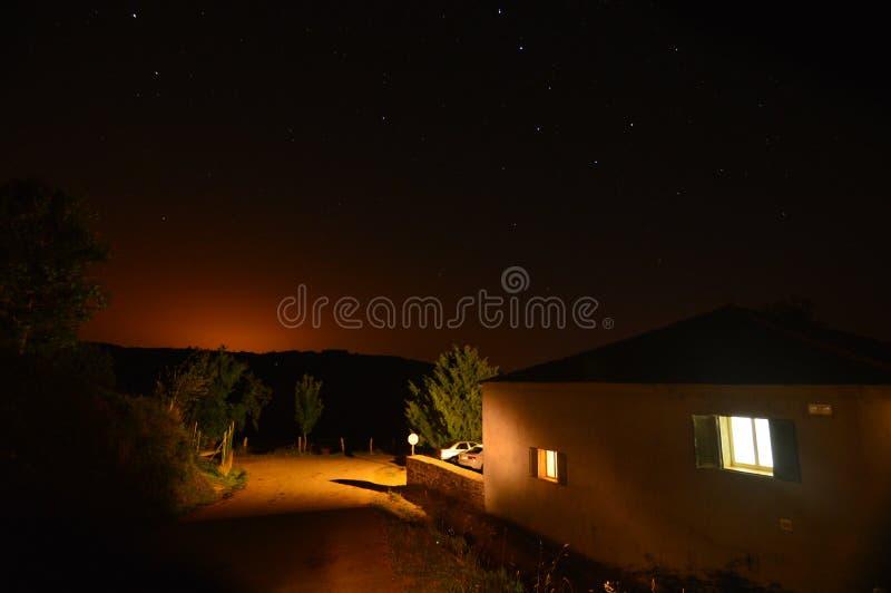 Spookhuis in de bergen van Galicië met de Cassiopeia-auto bovenop zijn dak en de zon wordt verloren die in de horizon verbergen d royalty-vrije stock foto