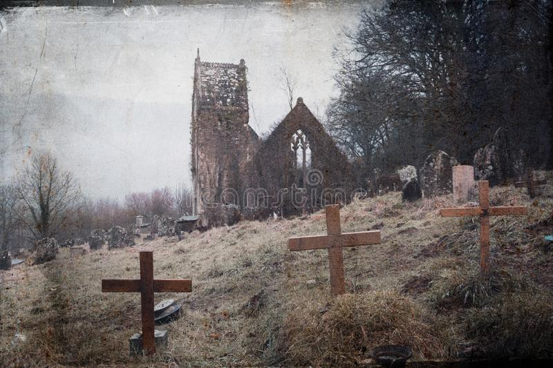 A spooky, abandoned graveyard with a ruined church in the background. With a blurred, vintage, grunge edit stock images