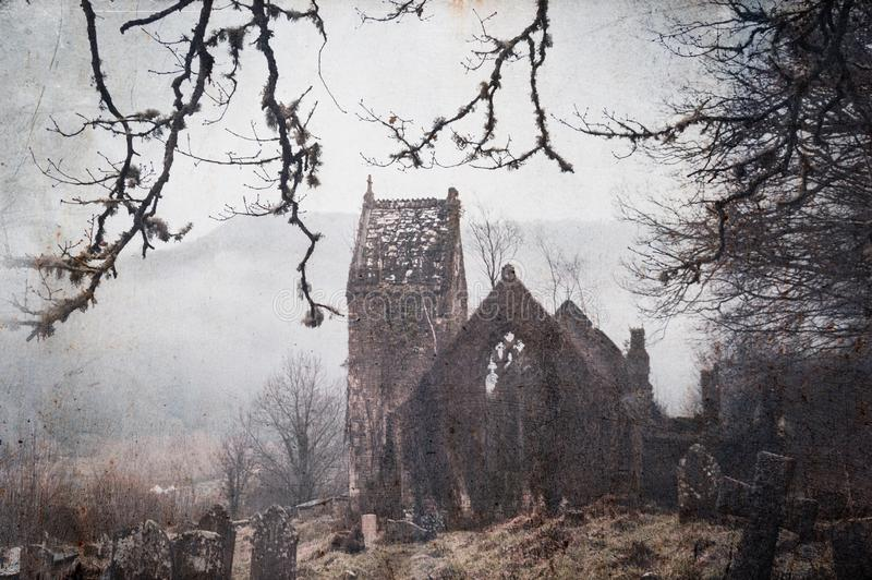 A spooky, abandoned graveyard with a ruined church in the background. With a vintage, grunge edit.  royalty free stock photography