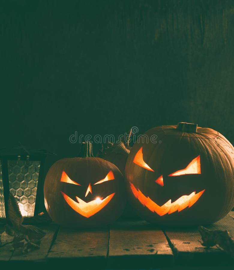 Spooky carving halloween pumpkins. On wooden plank. Halloween background royalty free stock photography