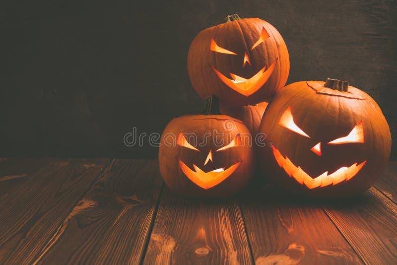 Spooky carving halloween pumpkins. On wooden plank. Halloween background stock photo