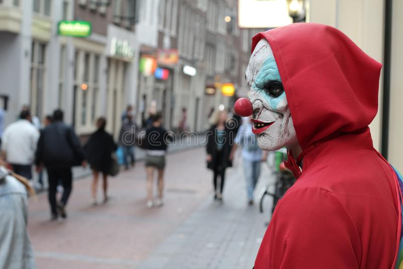 Spooky clown looking for his victim in crowded place royalty free stock photography