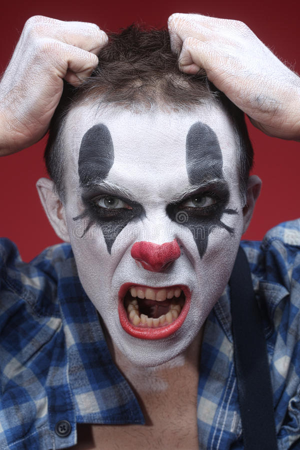 Spooky Clown Portrait on Red Background. Evil Spooky Clown Portrait on Red Background royalty free stock photography