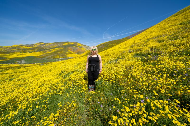 Spooky, creepy blonde woman wearing green alien sunglasses in a field of goldfield wildflowers in Carrizo Plain National Monument. During the California royalty free stock photos