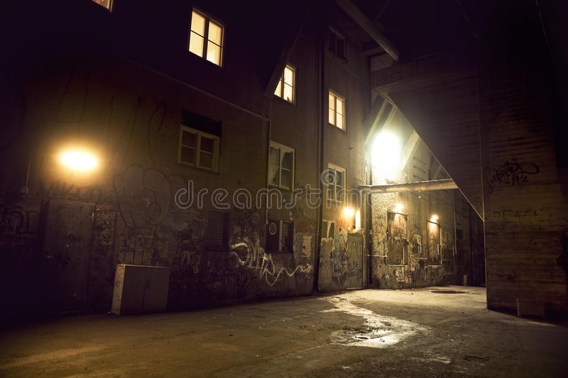 Spooky dark alley. Spooky messy dark alley with graffiti at night stock image