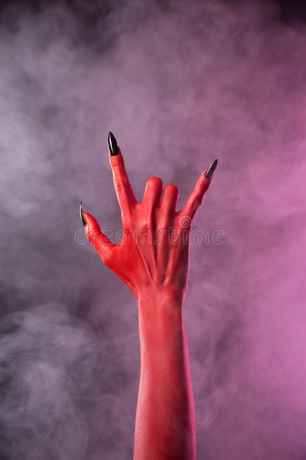 Spooky devil hand showing heavy metal gesture. Studio shot on smoky background royalty free stock photos