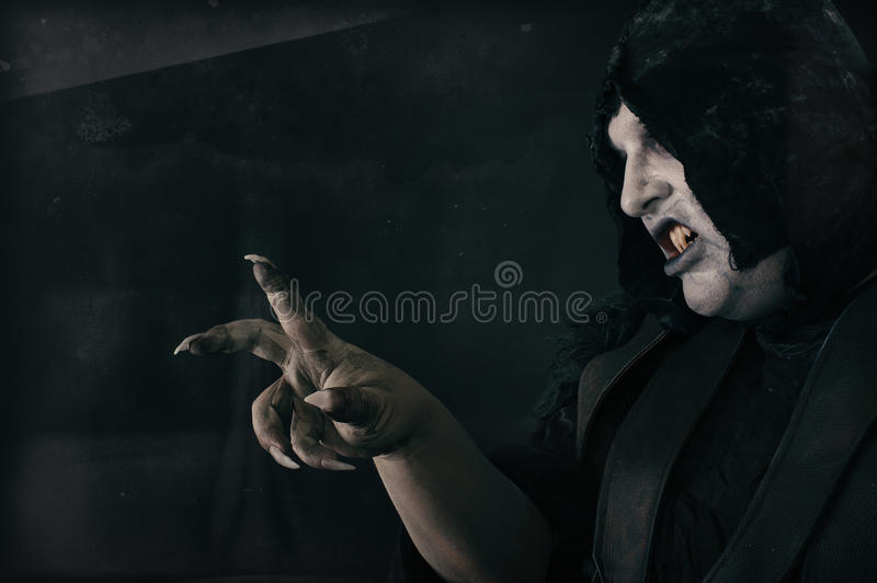 Spooky devil vamp with large scary nails. Hell and horror royalty free stock image