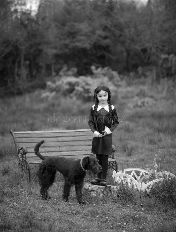 Spooky Girl and Dog. A little girl in black and a dog royalty free stock photo