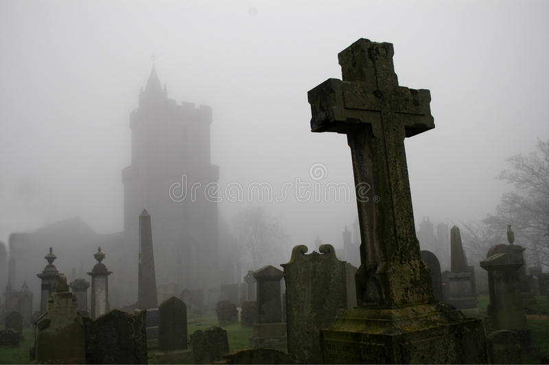 Spooky Graveyard. At Church of the Holy Rude in Stirling, with church outline in the mist and cross grave in foreground stock images
