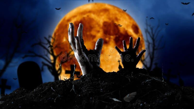 Spooky graveyard met zombie hand die uit de grond komt stock foto's