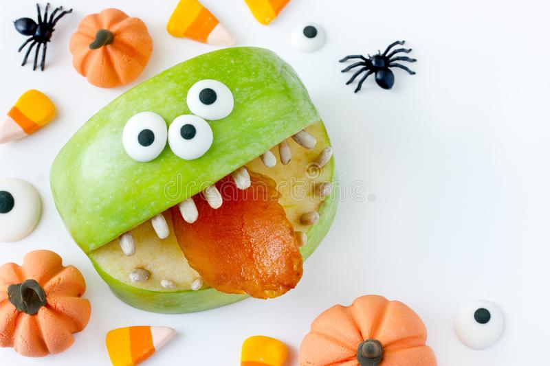 Spooky green apple monster for halloween. Party on white background with decorative pumpkins and spiders stock images