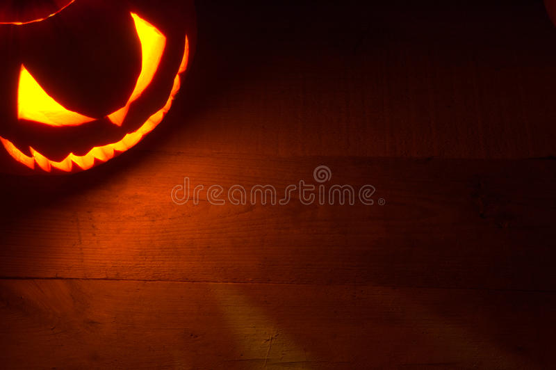 Spooky halloween background with evil face of jack o lantern in the corner. With red shadows on the wooden surface royalty free stock photography