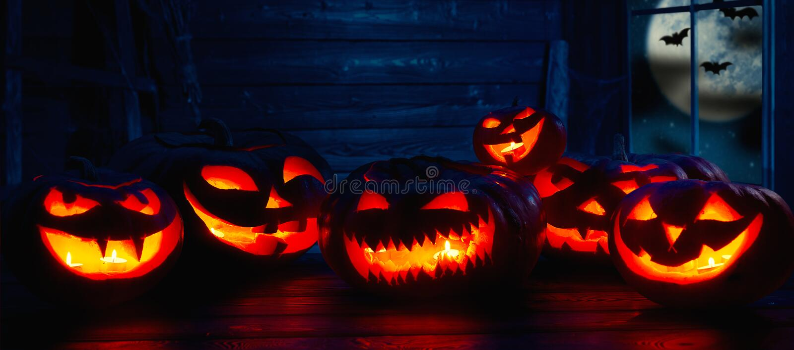 Spooky halloween background. scary pumpkin with burning eyes and. Smiles in the night stock photo