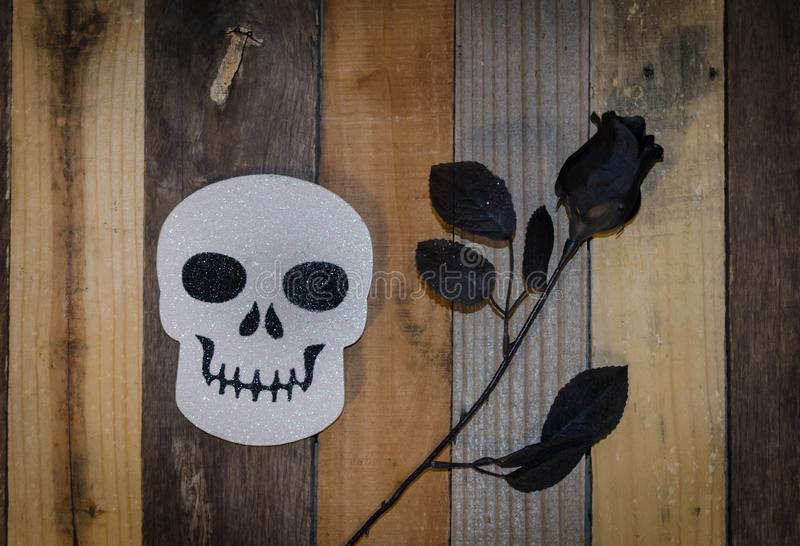 Spooky Halloween decoration. Halloween decoration of sparkling white skull and black rose. Fun and scary decor for this festive Autumn Holiday stock image