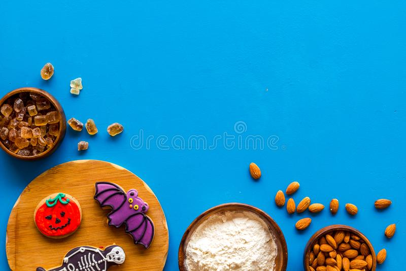 Spooky halloween figures with flour, sugar, almond for cooking treat on blue background top view mock up.  stock photos