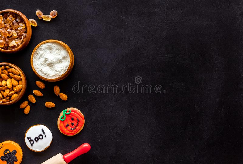 Spooky halloween figures with rolling pin, flour, sugar, almond for cooking treat on black background top view mock up.  stock photos