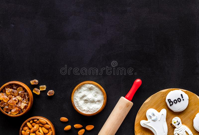Spooky halloween figures with rolling pin, flour, sugar, almond for cooking treat on black background top view mock up.  royalty free stock photos