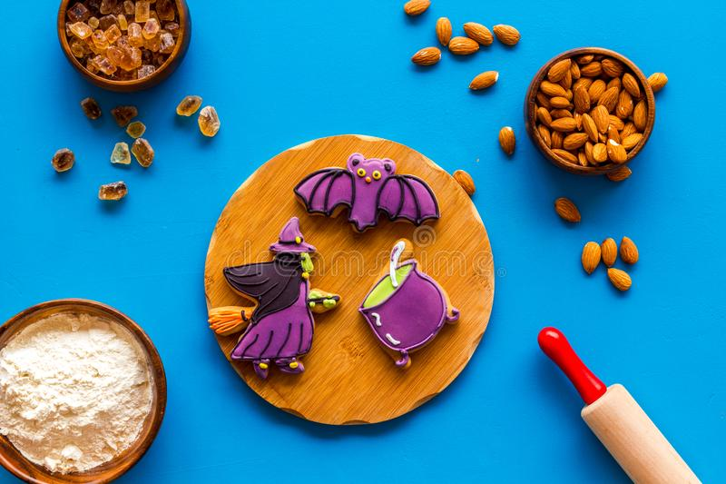 Spooky halloween figures with rolling pin, flour, sugar, almond for cooking treat on blue background top view.  stock photo