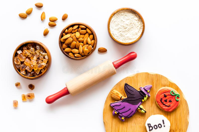 Spooky halloween figures with rolling pin, flour, sugar, almond for cooking treat on white background top view.  royalty free stock image