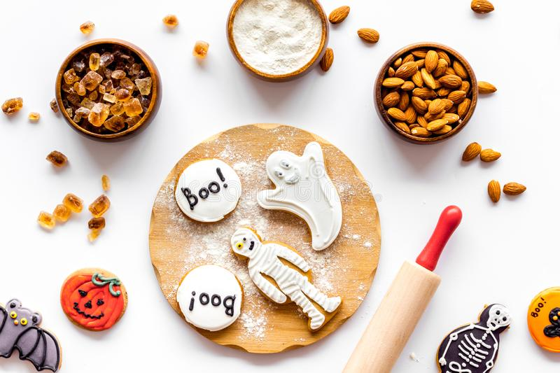 Spooky halloween figures with rolling pin, flour, sugar, almond for cooking treat on white background top view.  royalty free stock photo