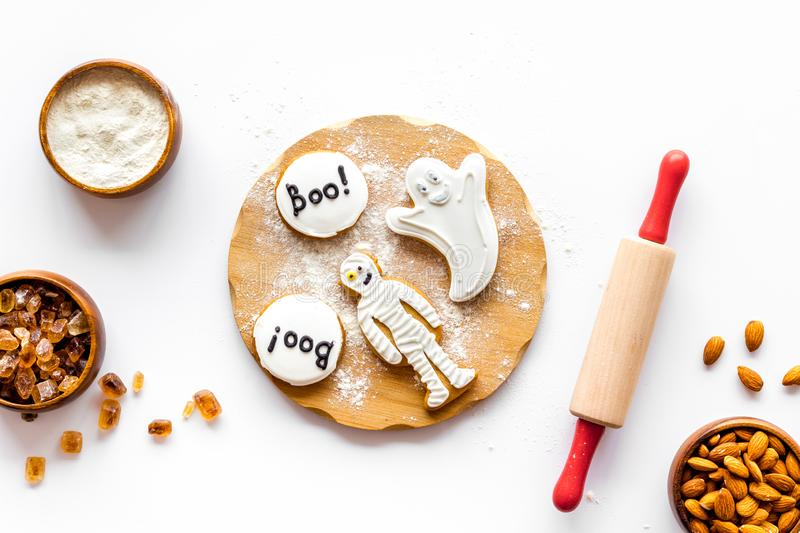 Spooky halloween figures with rolling pin, flour, sugar, almond for cooking treat on white background top view.  stock image