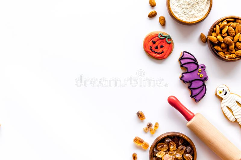 Spooky halloween figures with rolling pin, flour, sugar, almond for cooking treat on white background top view mock up.  stock photography