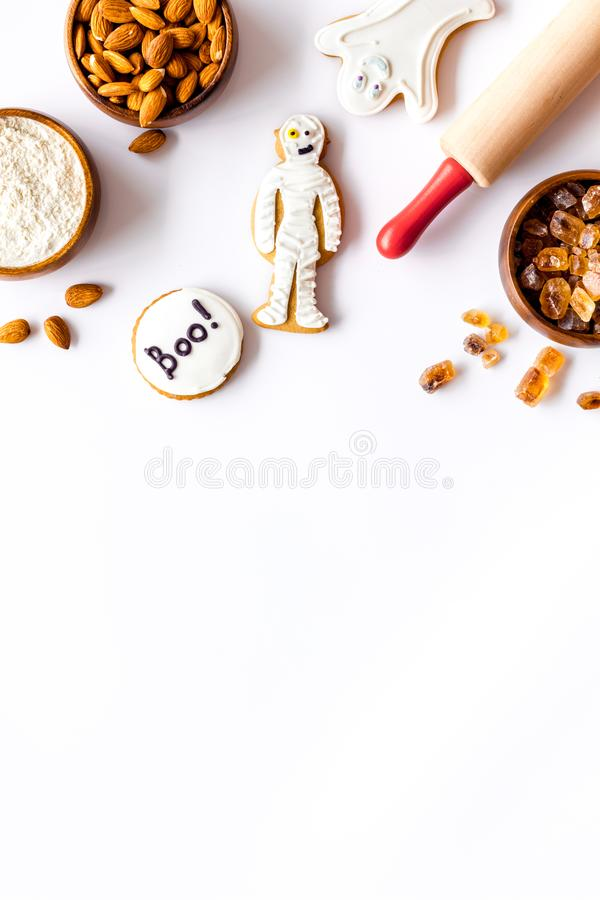 Spooky halloween figures with rolling pin, flour, sugar, almond for cooking treat on white background top view mock up.  stock image