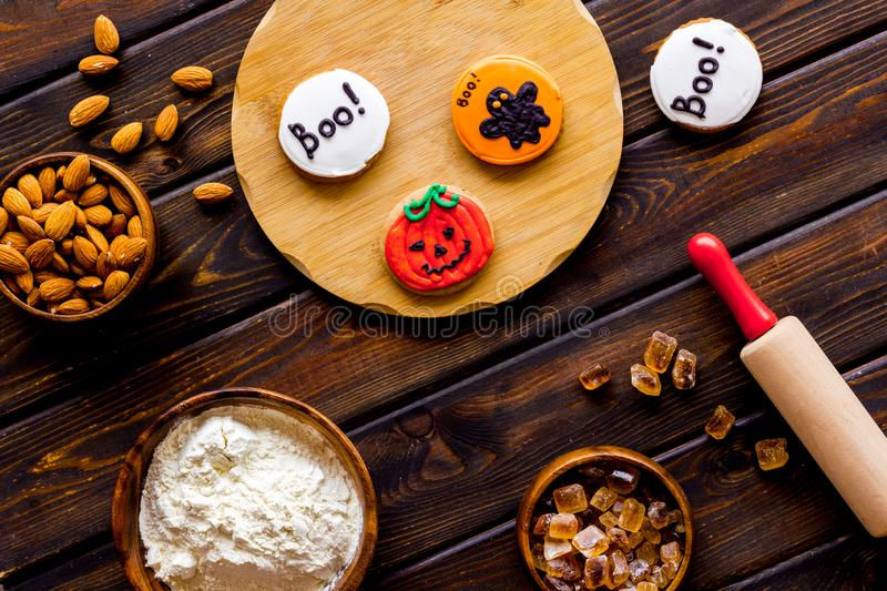 Spooky halloween figures with rolling pin, flour, sugar, almond for cooking treat on wooden background top view.  stock photo