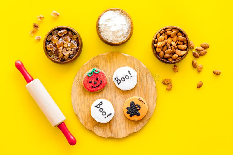Spooky halloween figures with rolling pin, flour, sugar, almond for cooking treat on yellow background top view.  royalty free stock image