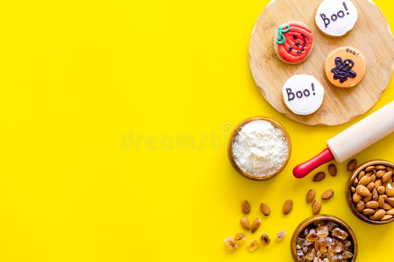 Spooky halloween figures with rolling pin, flour, sugar, almond for cooking treat on yellow background top view mock up.  stock photos