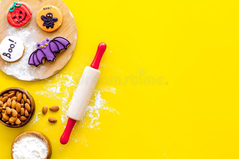 Spooky halloween figures with rolling pin, flour, sugar, almond for cooking treat on yellow background top view mock up.  royalty free stock image