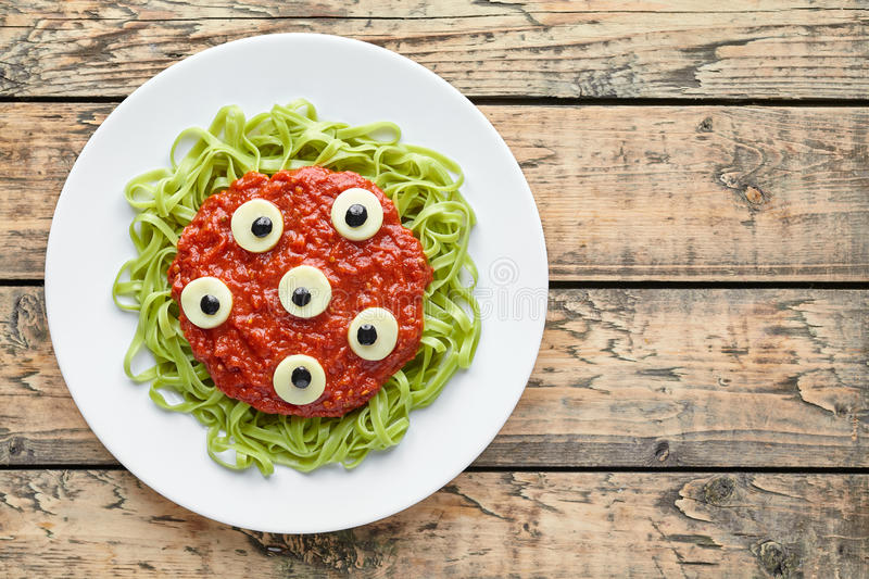 Spooky halloween monster green spaghetti pasta holiday decoration party food. With fake blood tomato sauce and many mozzarella eyeballs on vintage wooden table royalty free stock image