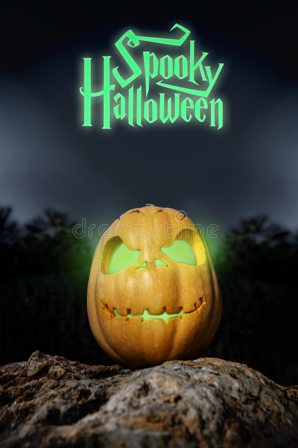 Spooky Halloween neon pumpkin in on a rock in the darkness. Spooky Halloween neon and scary pumpkin jack-o-lantern with a smile on a rock from bottom perspective royalty free stock photo