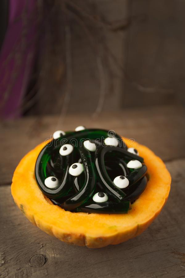 Spooky Halloween party food - gummy jelly worms in pumpkin with monsret eyes on wooden background, holiday party close up royalty free stock photos