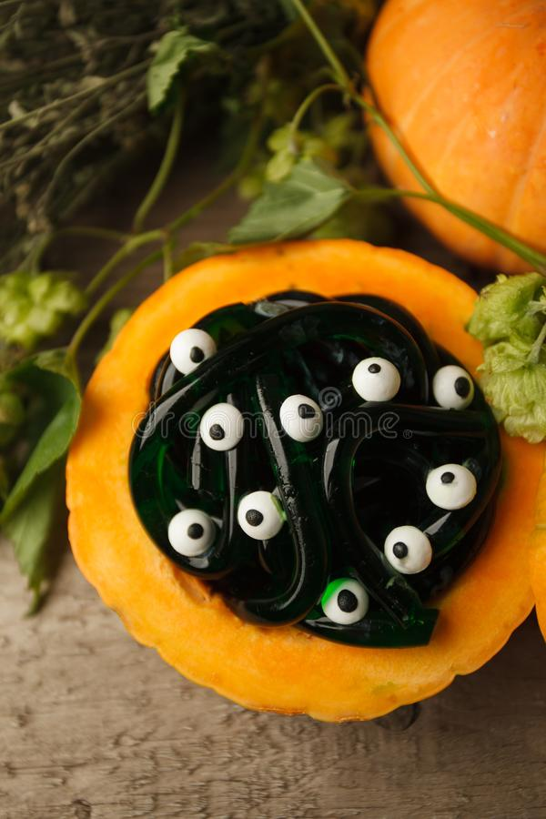 Spooky Halloween party food - gummy jelly worms in pumpkin with monsret eyes on wooden background, holiday party close up stock image